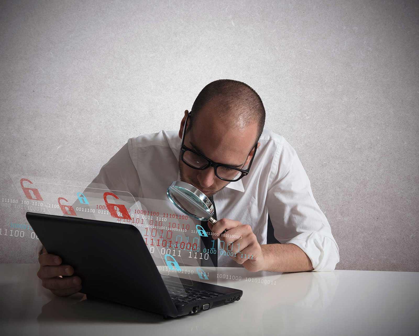 Hombre mirando con lupa un portátil