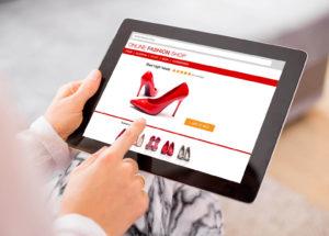 Mano de mujer realizando una compra online de zapatos desde un tablet