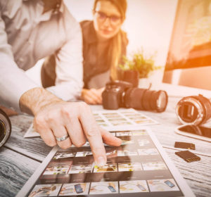 Dos fotógrafos eligiendo miniaturas de fotografías