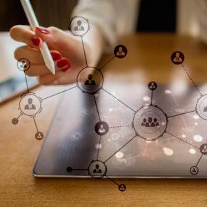 Foto de una mano y un ordenador con dibujos de redes sociales, significando la función del Community Manager