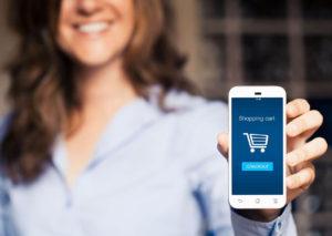 Mujer con un móvil en la mano enseñando carrito de compra de tienda online